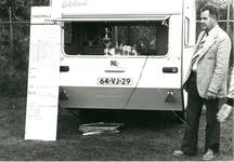 74 Foto van voorzitter H. Dijenborg bij de 'organisatiecaravan' tijdens het voetbaltournooi. Met bijlage