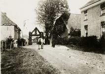 3188 Een onverharde weg in Wijnbergen met aan het eind een ereboog. Eerste pand rechts de pastorie die gebouwd werd in ...
